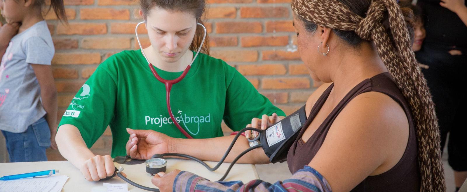 Voluntaria de medicina midiendo la presión sanguínea.